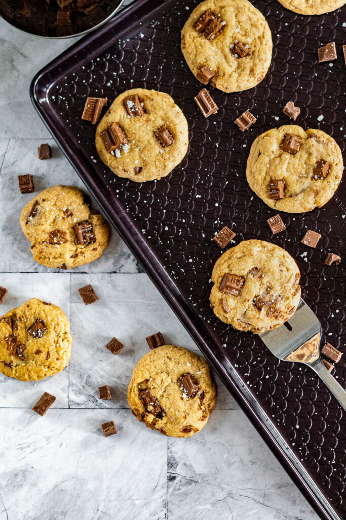 Scooping sourdough chocolate chip cookies off a baking sheet.