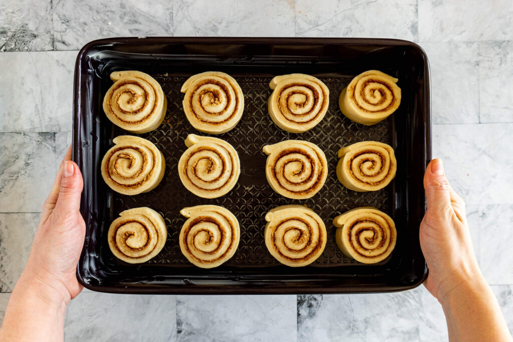 Prepared cinnamon rolls in a baking dish.