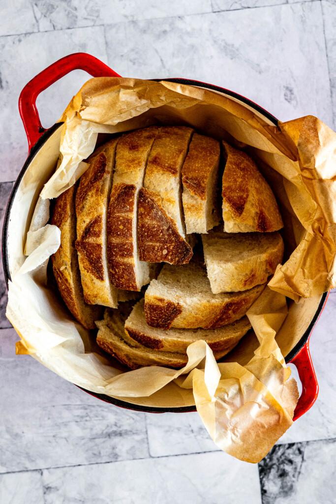 Sliced sourdough loaf in a dutch oven.