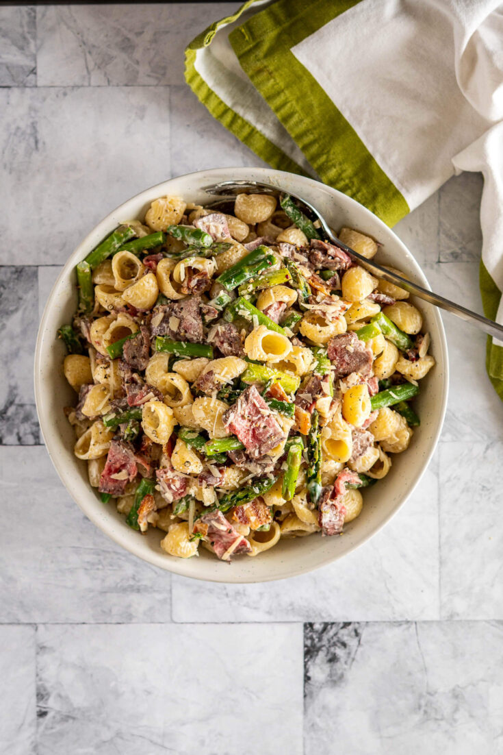 Overhead view of pasta salad with steak in a bowl.
