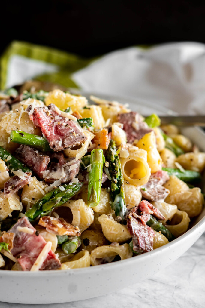 Side view of steak pasta salad in a white bowl.