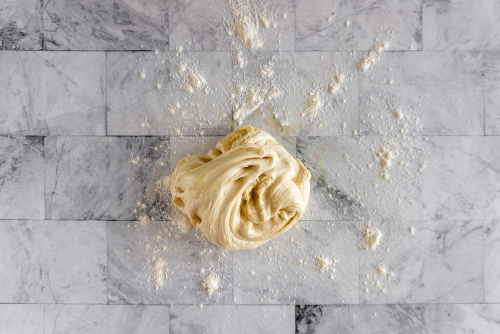 Cinnamon roll dough on a floured surface.