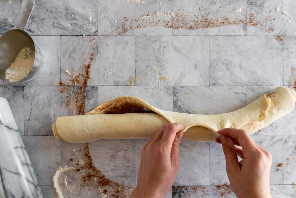 Sealing the cinnamon rolls.