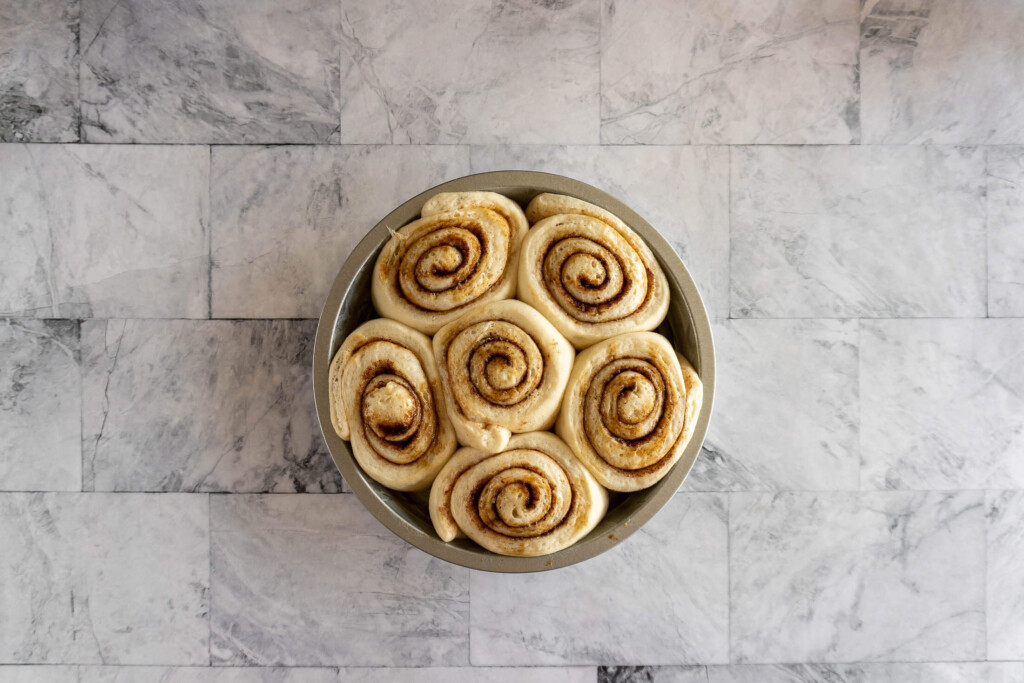Risen rolls in a round pan.
