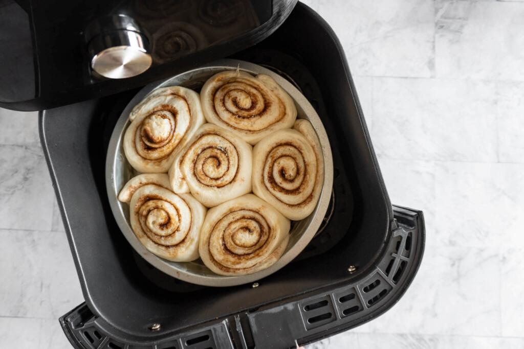 Risen cinnamon rolls in air fryer.