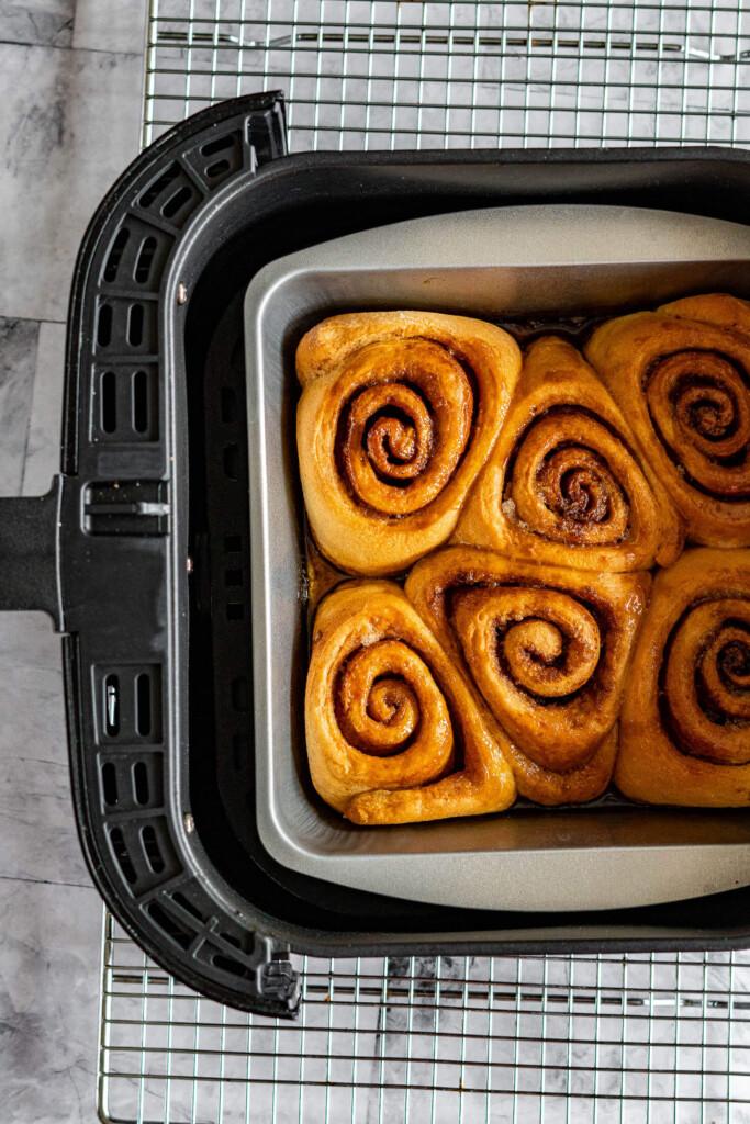 Cinnamon rolls in air fryer basket.