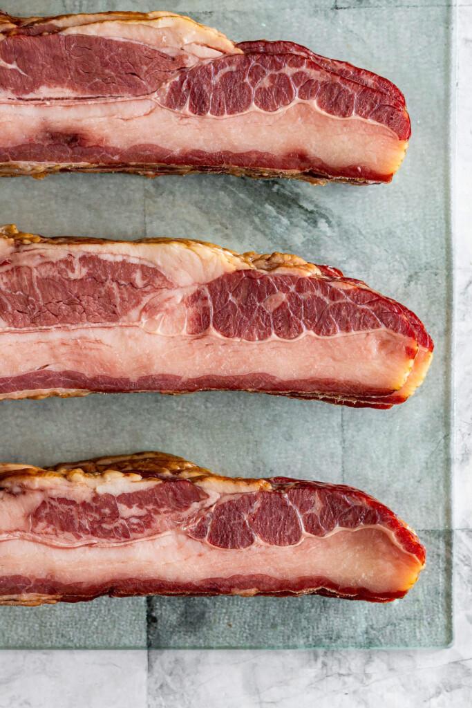 Sliced beef bacon on a cutting board.