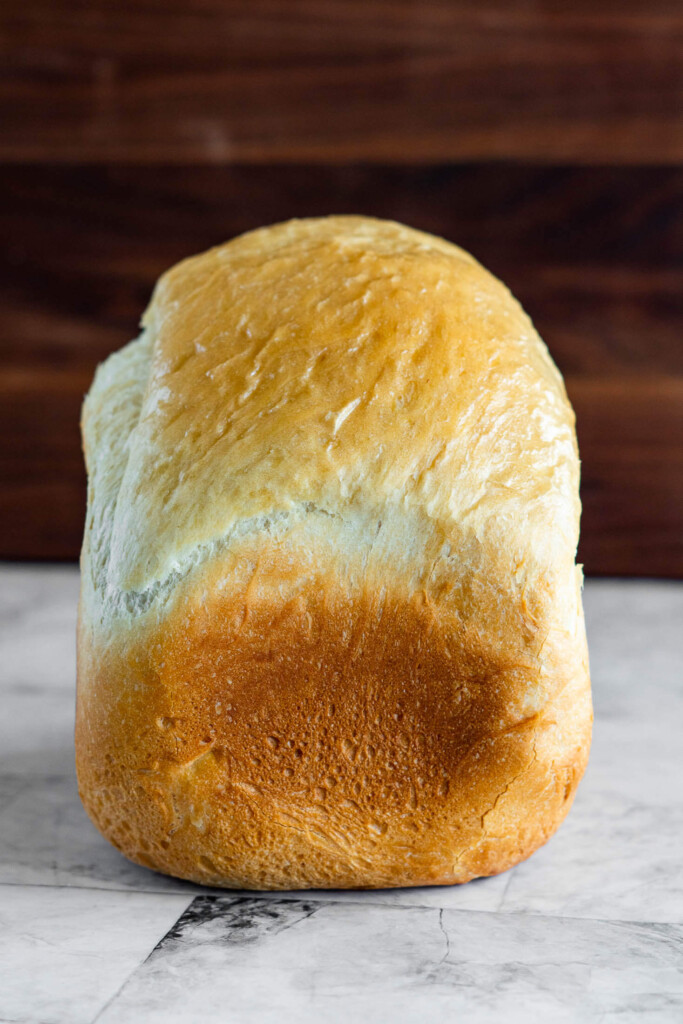 Side view of a loaf of bread machine bread made with sourdough discard.