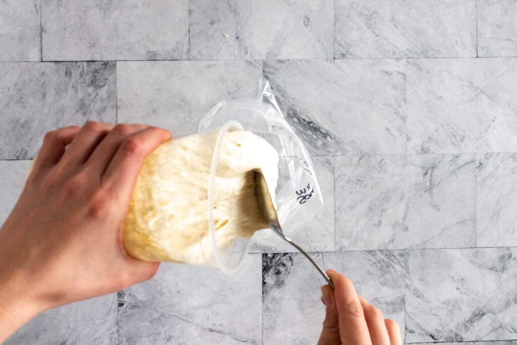 Scooping sourdough from a container into a ziplock bag.