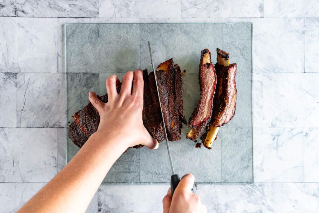 Slicing beef back ribs.
