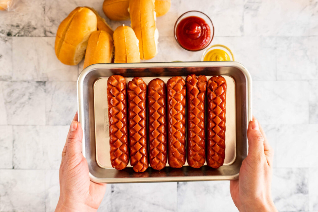 Fully cooked smoked hot dogs on an aluminum tray.