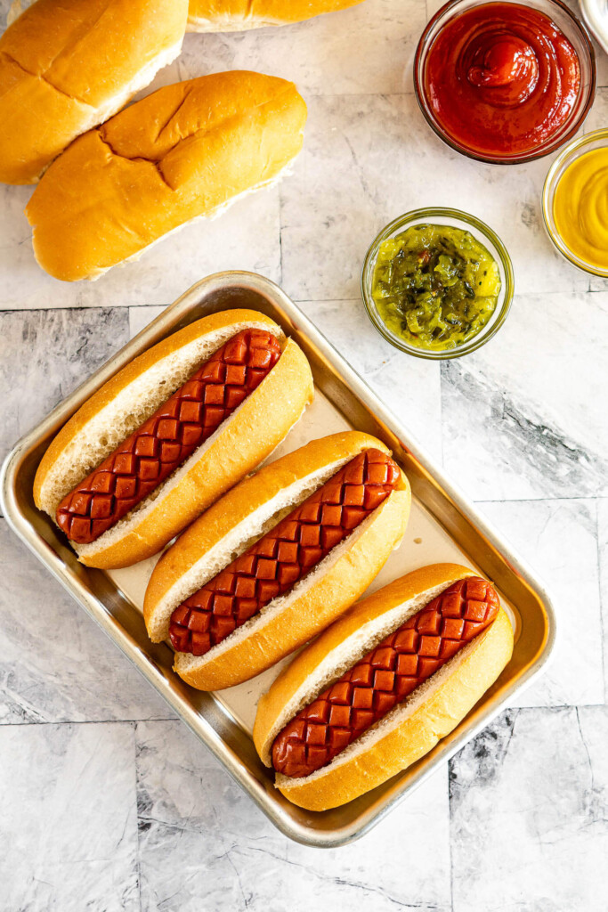 Scored smoked hot dogs in buns.