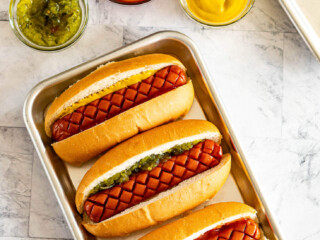 Smoked hot dogs in buns topped with mustard, relish, ketchup.