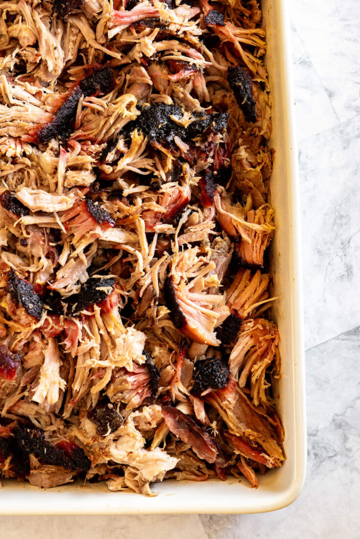 Smoked pulled pork shoulder in a white dish.