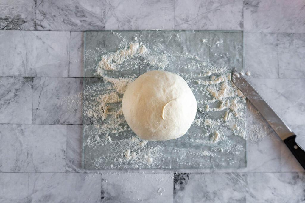 dough shaped into a boule on a floured cutting board.