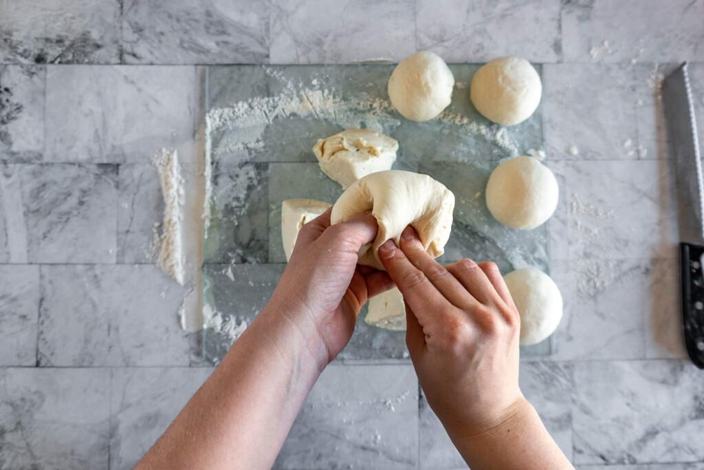 Shaping dough pieces into tight balls.