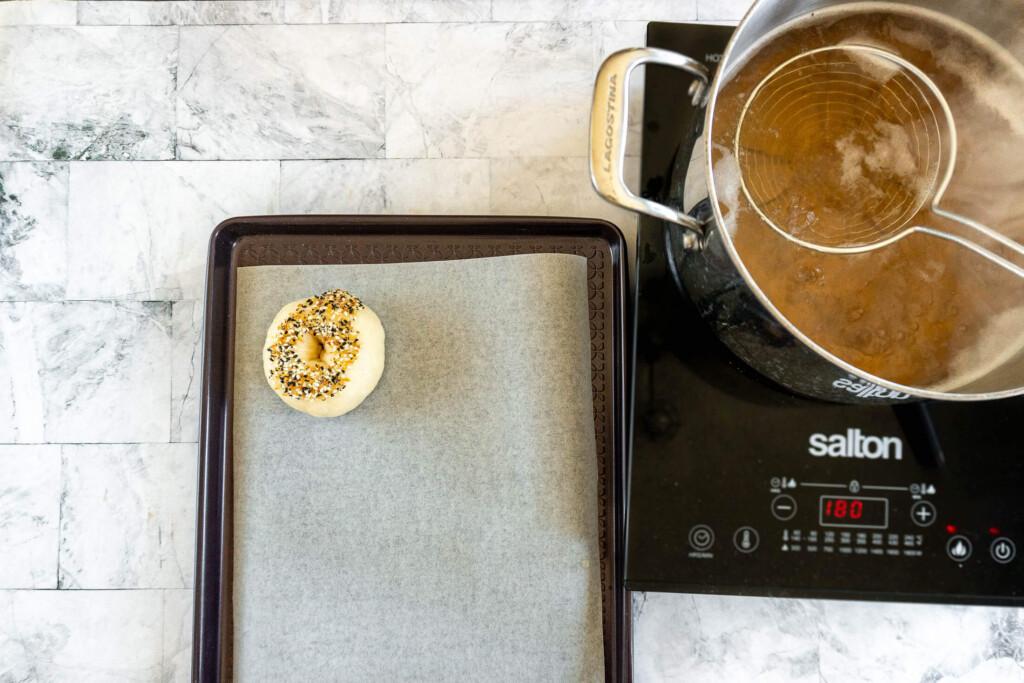 Seasoned boiled bagel on a prepared cookie sheet.