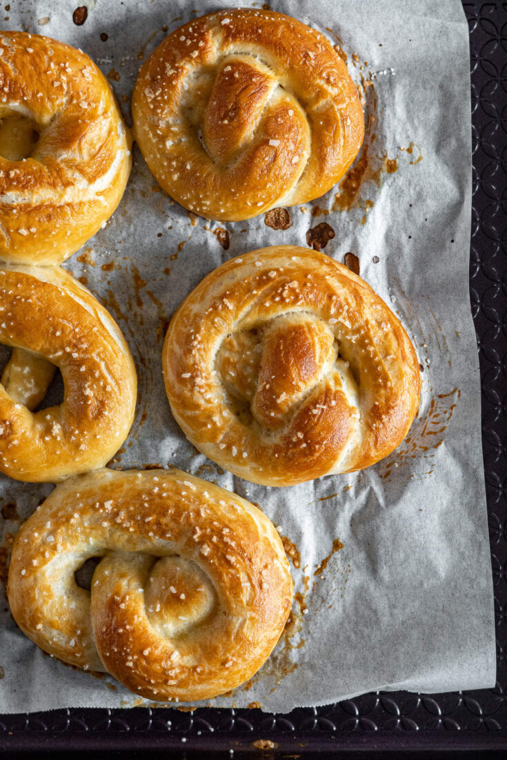 Overhead view of freshly baked sourdough pretzels on a baking sheet.