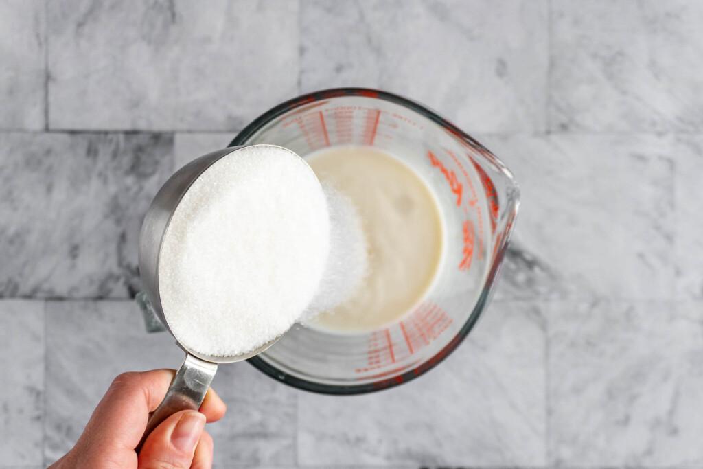 Adding sugar to the milk.