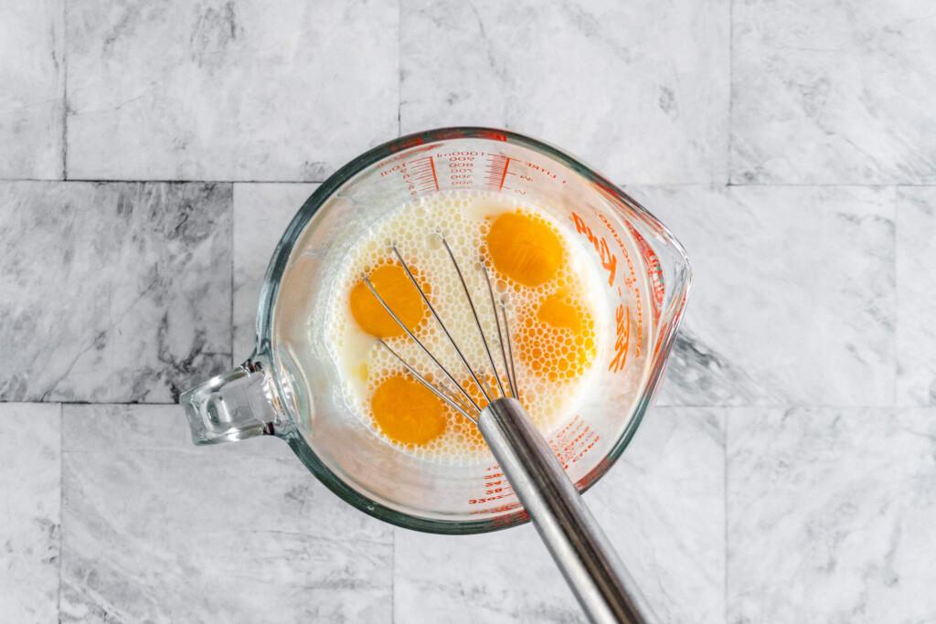 Whisking in the egg yolks.