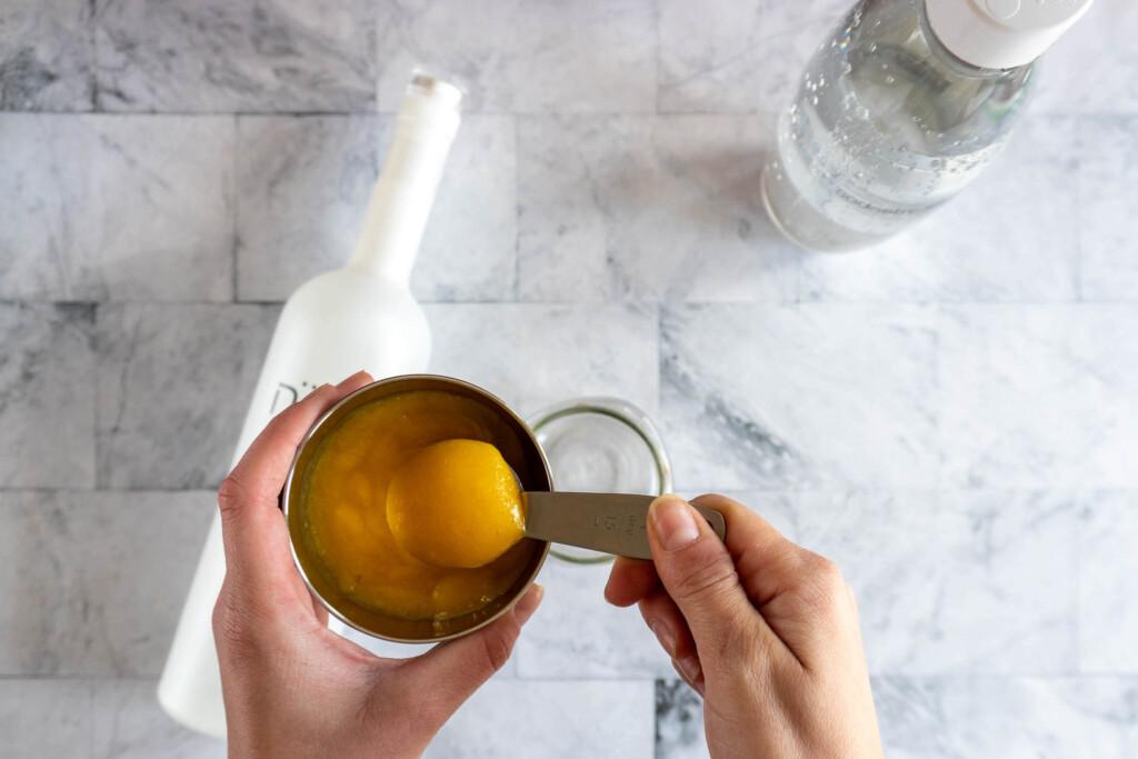 Adding mango puree to a mason jar.