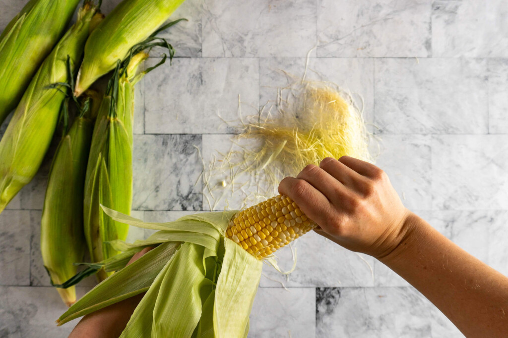 Rubbing the corn to remove the remaining tassels.