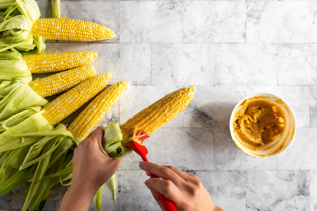 Brushing the bbq butter on the corn.