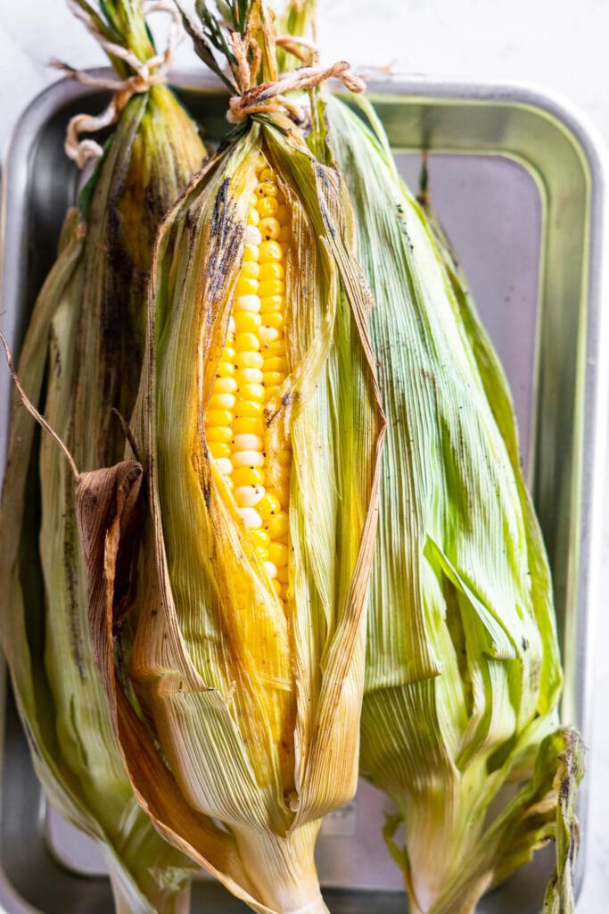 Kernels peeking out of a smoked corn cob.