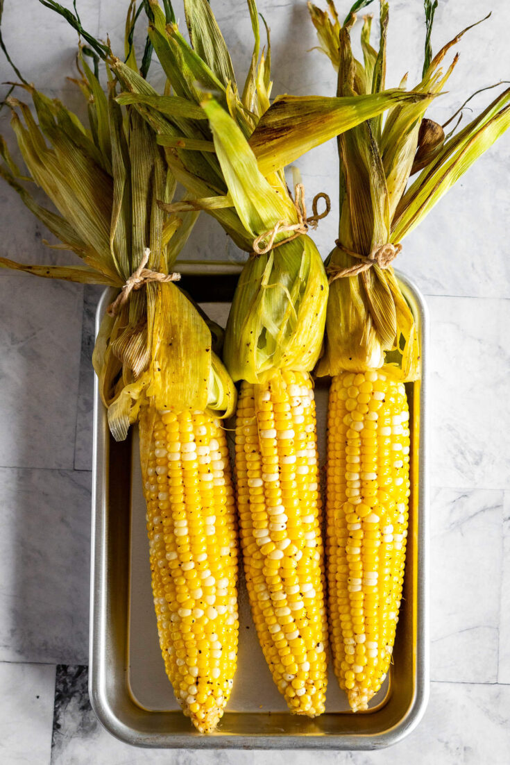 Open husks of smoked corn on the cob.