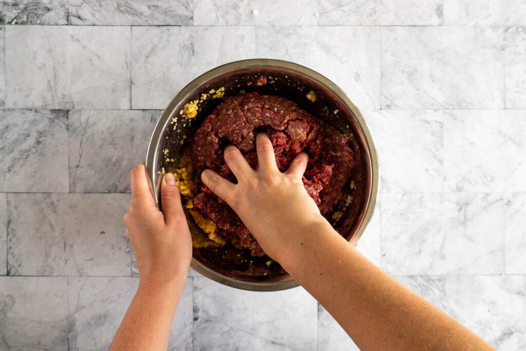 Mixing the ground beef into the breadcrumb mix.