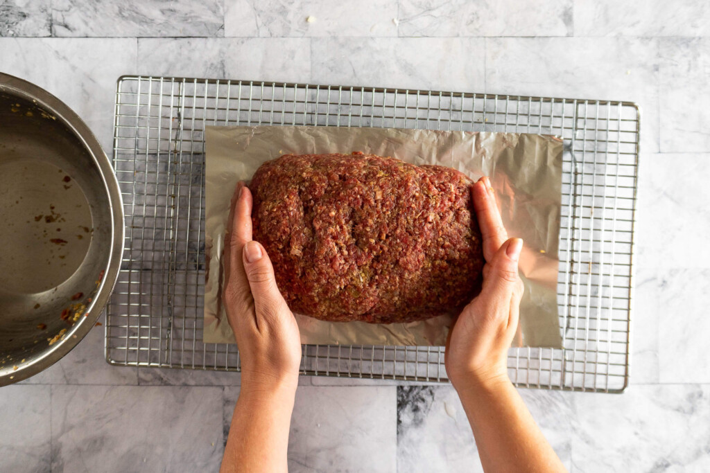 Shaping the meatloaf on the tinfoil base.