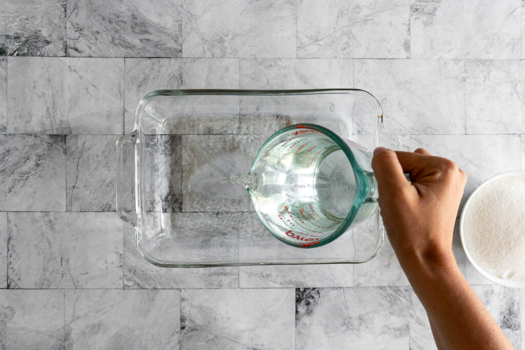 Pouring water into a 9x13 baking dish.