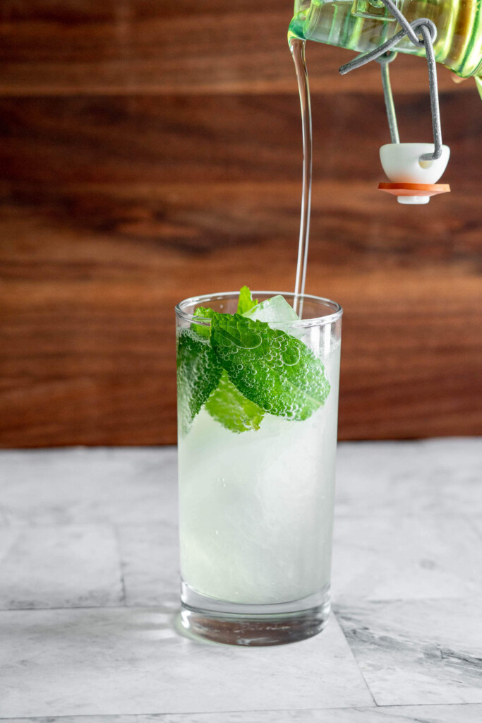 Pouring smoked simple syrup into a mojito.