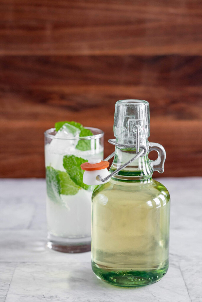 A jug of simple syrup beside a mojito.