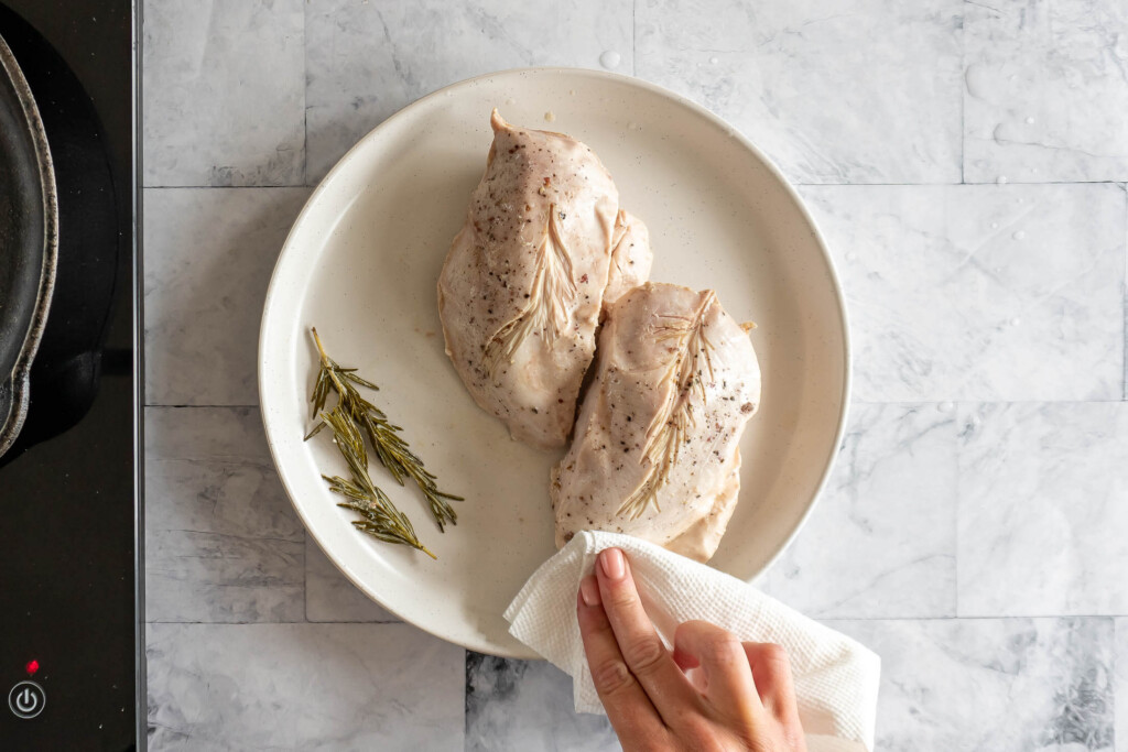 Blotting chicken breast with paper towel to remove moisture.