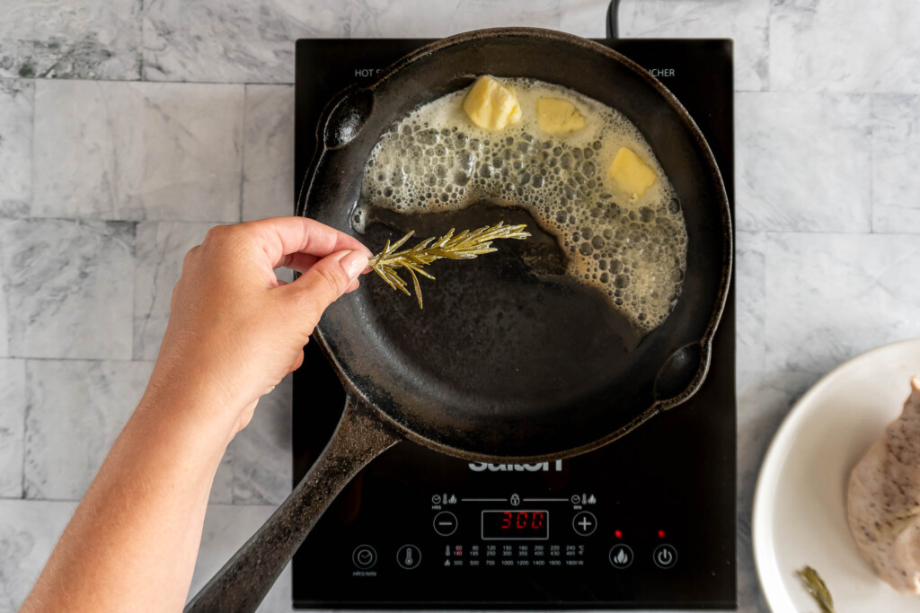 Adding rosemary from bag to butter in heated saucepan.
