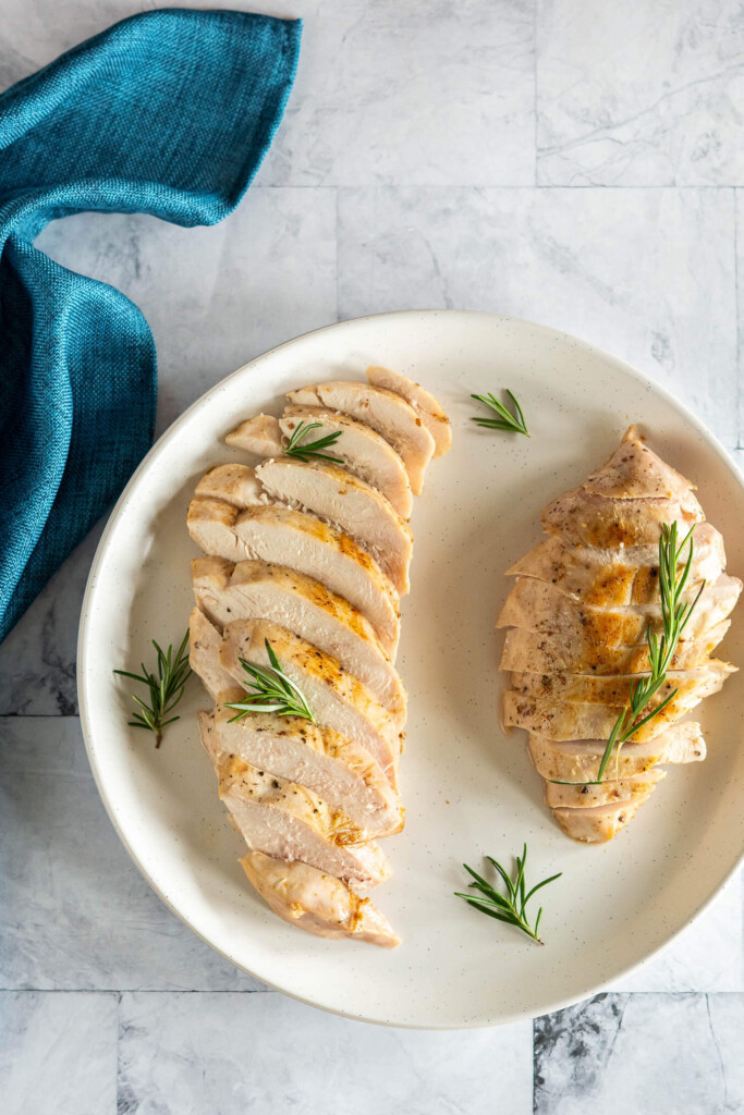 Sliced chicken breast on a plate garnished with rosemary.