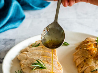 Drizzling poaching butter over the sous vide chicken breast.