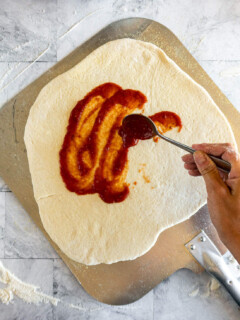 Smearing the pizza dough with pizza sauce.