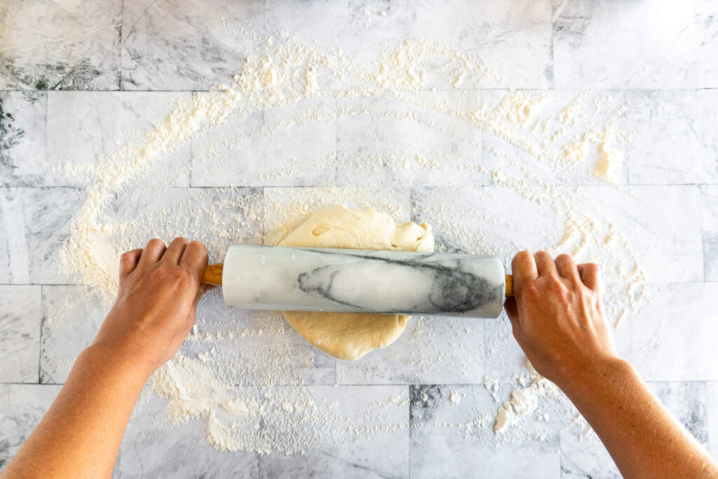 Rolling the pizza dough with a marble rolling pin.