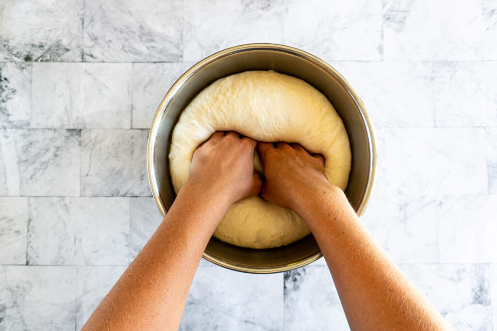 Punching down the pizza dough in a stainless steel bowl.