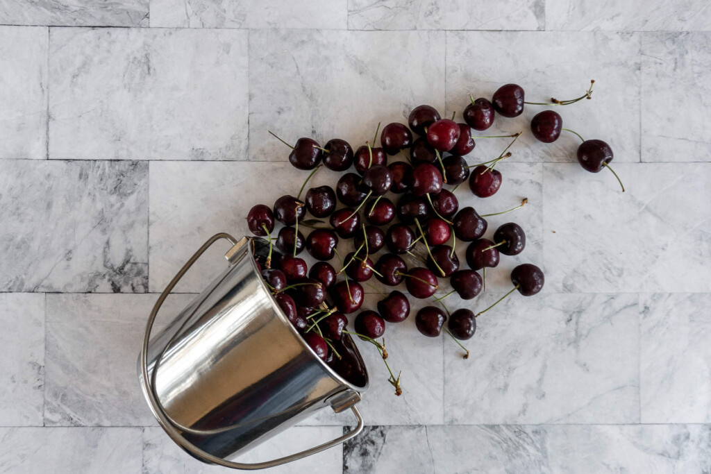 Fresh cherries spilling out of a bucket.