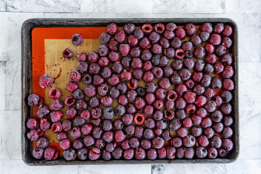 Frozen cherries on a prepared baking sheet.
