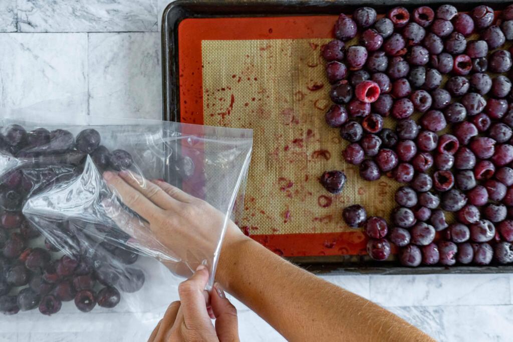 Transferring frozen cherries to vacuum seal bags.
