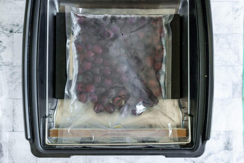 Cherries in an Avid Armor vacuum sealer ready to be sealed.