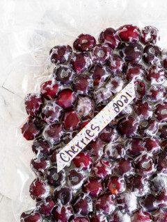 A vacuum sealed bag of frozen cherries labeled with the contents and the date.