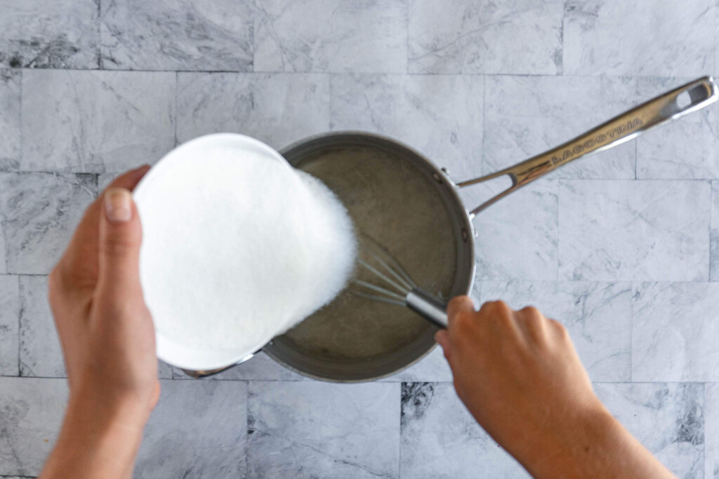 Whisking sugar into a pot with water to make simple syrup.