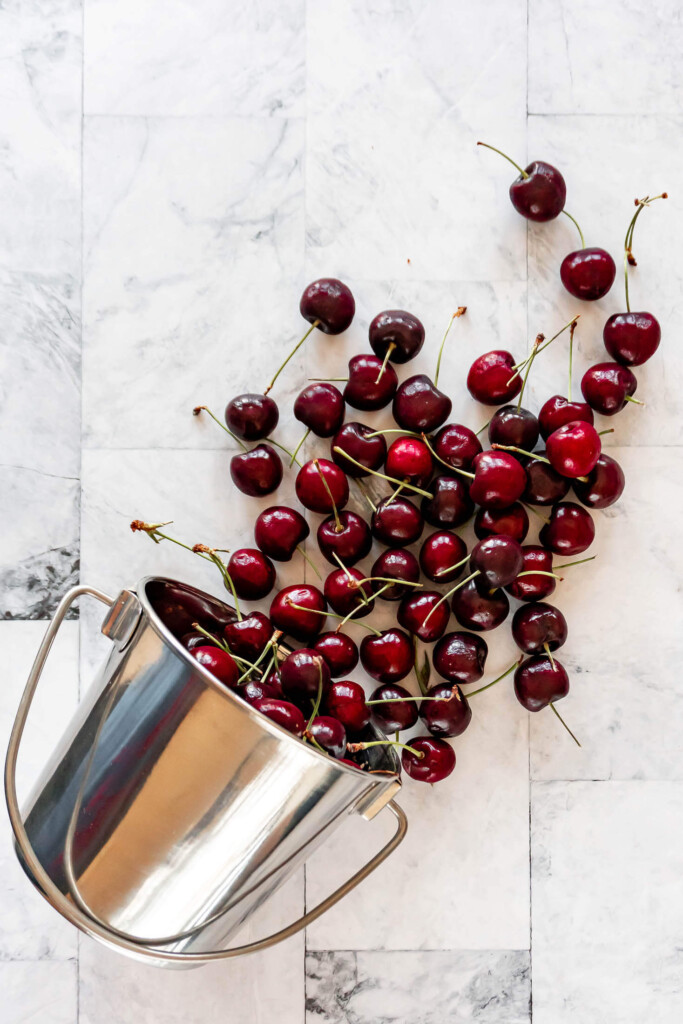 Cherries spilling out of a metal bucket.