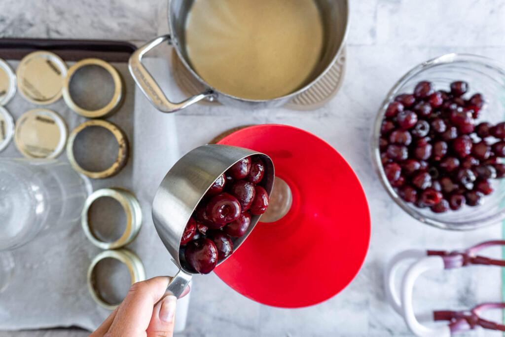 Adding cherries to the jar.