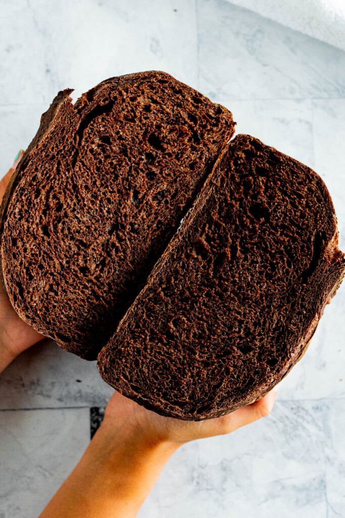 Hands holding a sliced loaf of chocolate sourdough.
